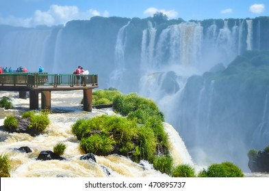 Iguazu falls national park on the border of Brazil and Argentina with tourists on wooden footbridges