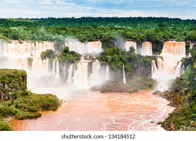 Iguazu falls, one of the new seven wonders of nature. UNESCO World Heritage site. View from the brazilian side showing the argentinean side, during rains season with brown water.