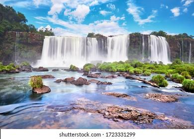 Iguazu Wasserfälle in Argentinien. Panoramasicht auf viele majestätische mächtige Wasserkaskaden mit Nebel und Reflexion des blauen Himmels mit Wolken. Panoramabild des Iguazu-Tals.