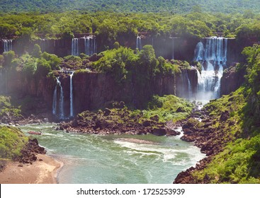Iguazu waterfalls in Argentina, view from above. Panoramic view of many majestic powerful water cascades with mist. Panoramic image of several waterfalls from above.