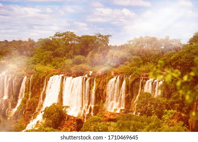 Iguazu waterfalls in Argentina, view from Devil's Mouth, powerful water cascades with mist on Iguazu river. Toned image with flare.