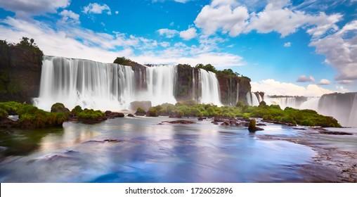 Cascadas de Iguazú en Argentina, vistas desde la boca del diablo. Vista panorámica de muchas majestuosas y potentes cascadas de agua con niebla. Imagen panorámica con reflejo del cielo azul con nubes.