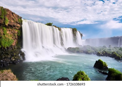 Iguazu waterfalls in Argentina, view from Devil's Mouth. Panoramic view of many majestic powerful water cascades with mist. Side view of the wide powerful waterfall. Turquoise water and stones.