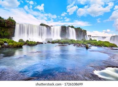 Iguazu Wasserfälle in Argentinien, Blick aus dem Mund des Teufels. Panoramasicht auf viele mächtige Wasserfälle mit Nebel und Reflektion des blauen Himmels mit Wolken. Panoramabild des Iguazu Tales.