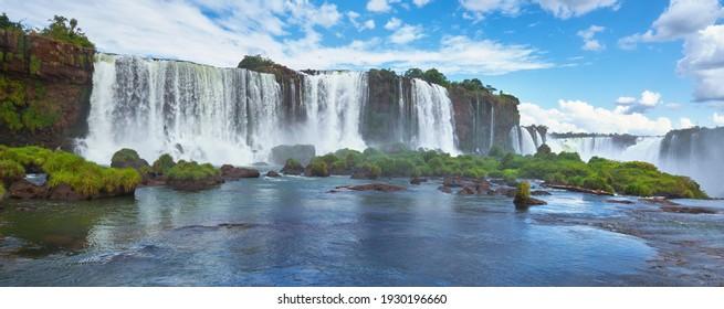 Iguazu Wasserfälle in Argentinien, Blick vom Teufels Mund. Panoramasicht auf viele majestätische mächtige Wasserkaskaden mit Nebel und Reflexion des blauen Himmels mit Wolken. Panoramabild des Iguazu-Tals.