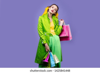 IImage of attractive shopper girl dressed in casual clothing, holding paper bags, standing isolated over pyrple background. Looking camera pointing