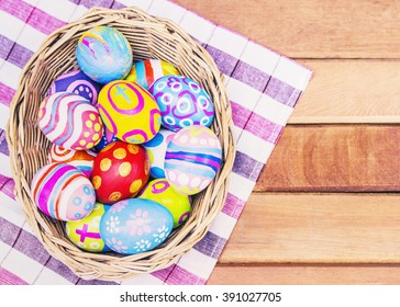iImage of Colorful painted Easter eggs in the basket with flowers on wooden background