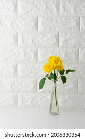 IImage of room with white walls, white table, yellow roses and photo frame.