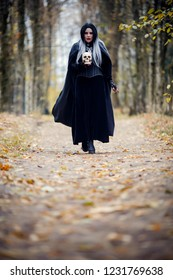 Iimage of witch woman in full growth in black cloak and with skull