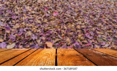 iimage of wood table and blur dry tropical almond leaf on the ground for background texture usage.