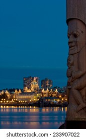 Iinner harbour and Parliament Buildings at dusk - Victoria, BC, Canada. Totem poles in the foreground