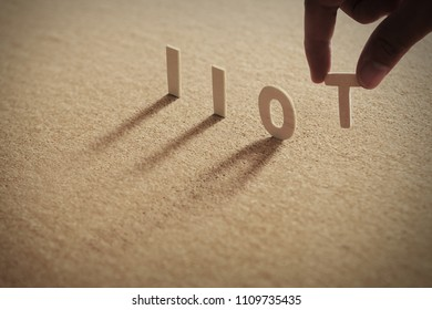 IIOT wood word on compressed or corkboard with human's finger at T letter.