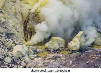 Ijen, Banyuwangi Regency, Java, Indonesia - February  9 2015: Sulfurous smokes from the volcano are the source of the sulfur mine. Sulfur miners are collecting the natural sulfur.