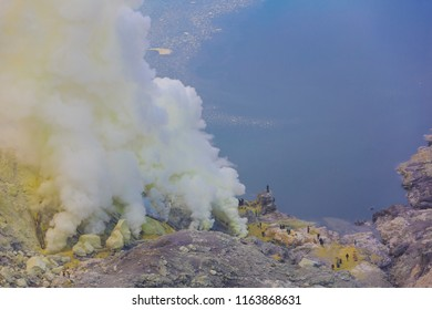 Ijen Volcano, Banyuwangi Regency, Java, Indonesia - February  9 2015: Sulfurous smokes from the volcano are the source of the sulfur mine. Sulfur miners are collecting the natural sulfur.