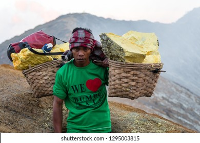 Ijen Volcano, Banyuwangi Regency, Java, Indonesia - February  9 2015:  Indonesian sulfur miner is carrying his 90-kg-load of sulfur from the floor of the volcano to the valley where he is getting paid