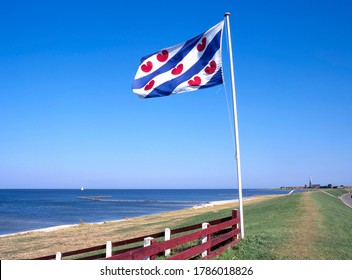 IJsselmeer coast with the flag of Friesland and at the horizon Hindeloopen, Friesland, Netherlands