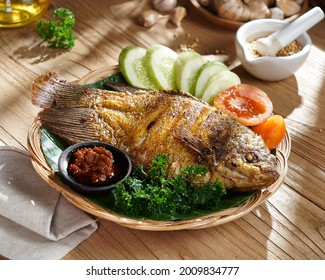 """""""Ikan Gurame Goreng"""" or fried freshwater fish with chilli sauce and vegetable. Serving on wooden table. Indonesian food and cuisine."""