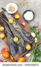 Ikan Lele segar or fresh cat fish on wooden chopping board with some spices, tomato, chili, shallot, garlic, and lime. Popular Indonesian fish to make Pecel Lele or lele Goreng with sambal.