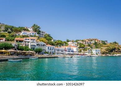 Ikaria Island, Evdilos, Sporades/ Greece – 08 02 2017: Beautiful sunny village town white house and harbor view to the greek blue sea with crystal clear water and fishing boats cruising yacht at shore