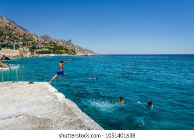 Ikaria Island, Karkinagri, Sporades/ Greece – 07 31 2017: Beautiful sunny village town harbor view to the greek blue sea with crystal clear water and kids children playing swiming jumping from shore