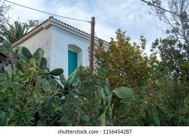 in the ikaria island, part of greek house with traditional decorations between trees.