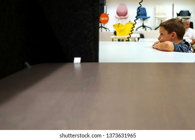 IKEA, New Haven, CT USA. Sept 2018. A young boy bored with head and arms slumped on a display table as parents shop at this world famous home furnishings outlet.