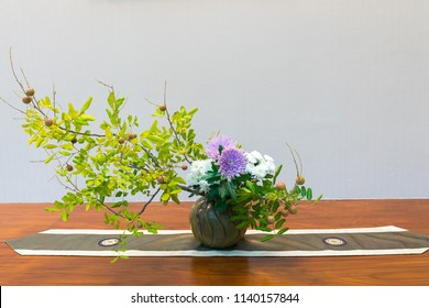 Ikebana, colorful flower in vase on wooden plate.Japanese style ,Ikebana is the Japanese art of flower arrangement. It is more than simply putting flowers in a container .Decorative item concept
