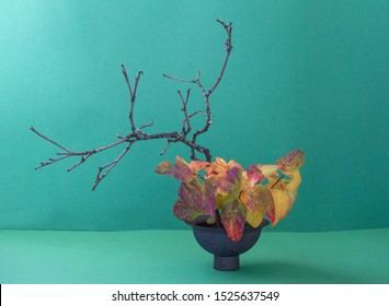 ikebana in a japanese vase on a green background