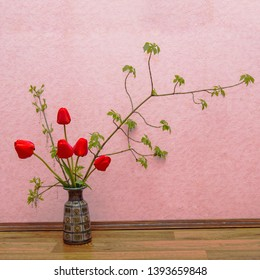 Ikebana with red tulips and ash-tree branches