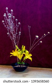 Ikebana with yellow lilies and dry herbs