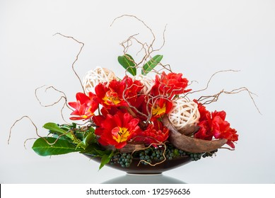 Ikebana-like artistic flower arrangement in a container on a glossy table