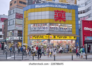 """IKEBUKURO, TOKYO - AUGUST 28, 2014: Matsumoto Kiyoshi drug store. Its vivid yellow color and red Japanese character (means """"medicine"""") can be seen every corner of downtown Tokyo."""