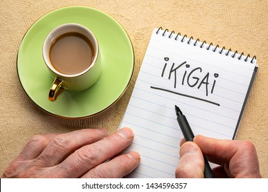 ikigai, a reason for being - man hand writing a note with a black marker in a spiral notebook