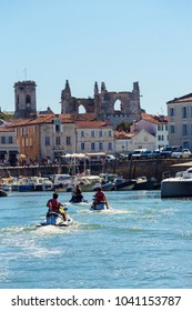Ile de re, France - August 22, 2016 : Rear view of young tourists returning from a walk at sea and returning to the port of St. Martin with their jet ski.