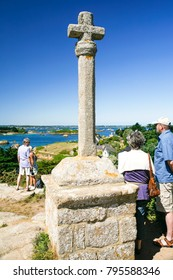 ILE-DE-BREHAT, FRANCE - JULY 4, 2010: tourists at viewpoint near Celtic cross on Brehat island. Ile-de-Brehat is island and commune located near Paimpol town, a mile from northern coast of Brittany