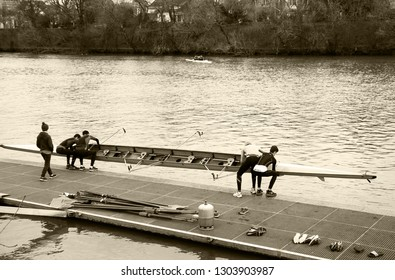 ILE-DE-FRANCE, FRANCE - JANUARY 26, 2019: Junior rowers training at Marne river. Boys carrying and getting the boat in the water. Sepia photo.