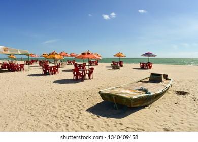 Ilha de Itamaraca, Brazil - Circa December 2018: Old jangada (typical boat) and beach bar tables and parasols on Itamaraca Island