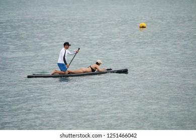 Ilhabela, Sao Paulo, Brazil; September 30 2018: Sup Paddle in Ilhabela. Man paddling on the table and woman enjoying the trip.