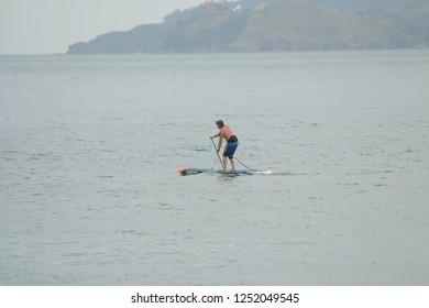 Ilhabela, Sao Paulo, Brazil; September 30 2018:  Man paddling alone doing Sup Paddle in the sea.