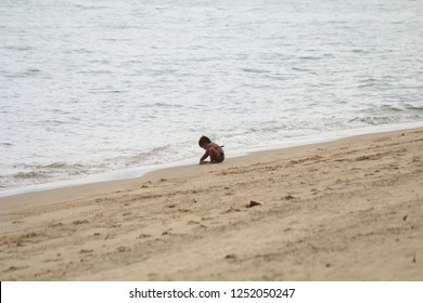 Ilhabela, Sao Paulo, Brazil; September 30 2018: Little brunette girl playing alone on the beach in front of the sea.