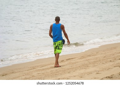 Ilhabela, Sao Paulo, Brazil; September 30 2018: Brunette man walking by the sea.