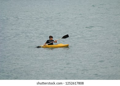 Ilhabela, Sao Paulo, Brazil; September 30 2018: Teenager paddling in kayak at sea.