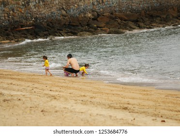 Ilhabela, Sao Paulo, Brazil; September 30 2018: Father playing with his twin daughters by the sea.