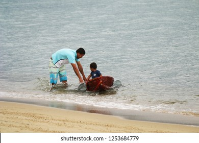 Ilhabela, Sao Paulo, Brazil; September 30 2018: Father playing with his little son with a boat by the sea.
