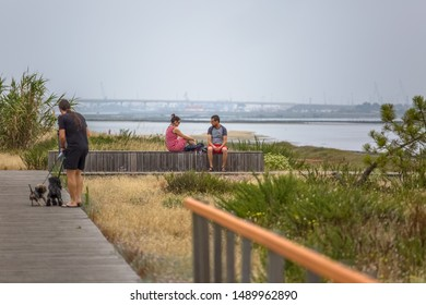 Ilhavo / Aveiro / Portugal - 07 19 2019 : View of pedestrian path with people, man walking dogs and couple sitting on wooden bench and enjoying river, bridge view as background