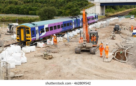 ILKESTON, ENGLAND - AUGUST 1: A train passes by construction workers on site next to a section of railway track. In Ilkeston, Derbyshire, England. On 1st August 2016.