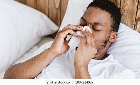 Ill Black Man Blowing Runny Nose In Paper Tissue Having Rhinitis Lying In Bed At Home. Sick African Guy Sneezing Having Sinusitis, Flu And Cold Symptom Concept. Panorama