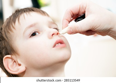 ill boy with flu and drops in the nose