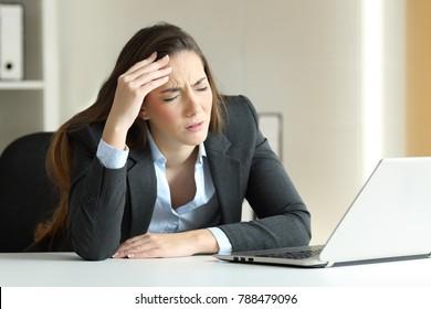 Ill businesswoman suffering migraine sitting in a desktop at office