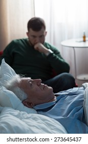Ill father lying in hospital bed and his worried son
